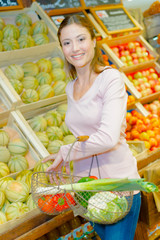 Lady shopping, standing next to melons