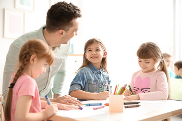 Cute little children with teacher in classroom at school