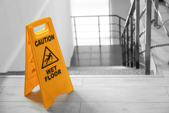 Safety sign with phrase Caution wet floor near stairs. Cleaning service