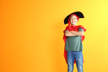 Adorable little child playing pirate on color background. Indoor recreation