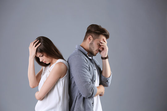 Upset young couple on grey background. Relationship problems