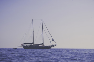 Vintage background of sailing boat on plain ocean and sky