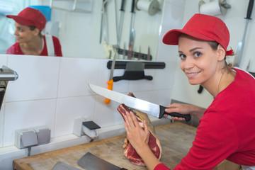 female butcher cutting meat