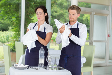 female and male bartenders cleaning glasses