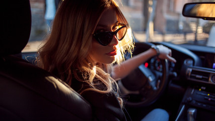 Beautiful young woman in sunglasses sitting behind the wheel of a car. Photo from the back seat