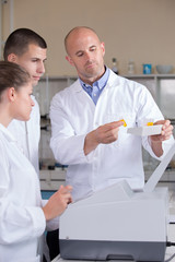 teacher in chemistry lab showing samples to his students