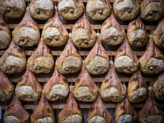 Thighs of ham during the seasoning process hanging in a cellar.