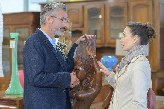 woman enquiring to antique dealer about wooden scupture