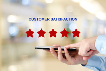 Man hand holding smart phone and red five star over blur background, customer excellent rating satisfacation, customer feedback