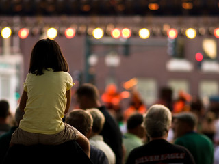 Young girl on her dad's shoulders at a concert