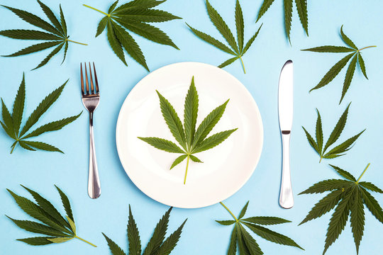Medical concept table setting with cutlery and cannabis leaves on blue background.