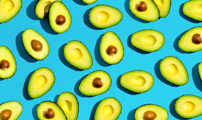 Wall Mural - Fresh avocado pattern on a blue background flat lay