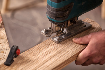 Close up of an experienced carpenter in work clothes and small buiness owner  is carving a wooden board on an  modern  hand drill in a workshop , in the background a lot of tools