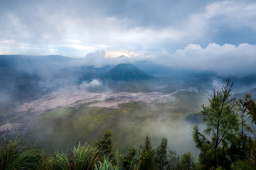 view of Mount Bromo under cloudy sky with the sand sea