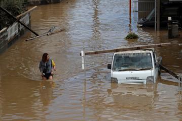 Women make their way in a flooded area in Mabi town in Kurashiki