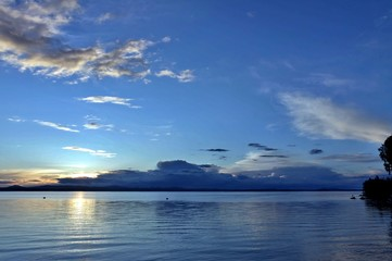 dark blue evening sky over the lake, orange sun