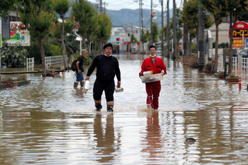 Men make their way in a flooded area in Mabi town in Kurashiki
