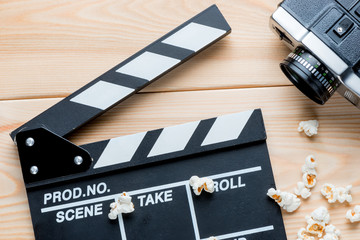 open video clapper, retro video camera and salted popcorn top view on wooden boards