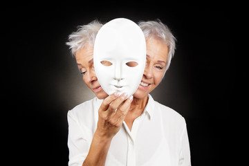 older woman hiding happy and sad face behind mask, concept for manic depression or bipolar or dramedy comedy drama