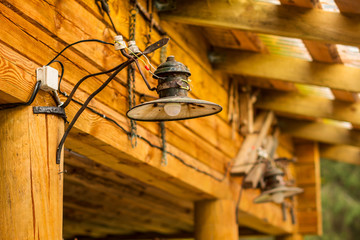 Old rusty lamp at the wood wall of the house