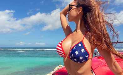 Sexy woman in american patriotic bikini near  red retro car at the Bali island sunny beach