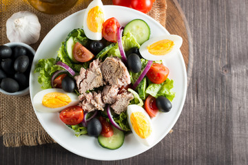 Fresh fish tuna salad made of tomato, ruccola, tuna, eggs, arugula, crackers and spices. Caesar salad in a white bowl on wooden background