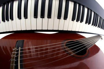 piano keys and classical guitar close up on white background