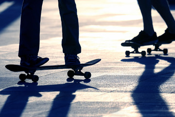 silhouette of people riding on a skateboard in the sun
