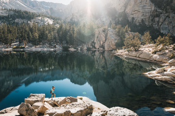 young man in  Yosemite, USA: Mountain landscape with mirror lake surrounded by high peaks