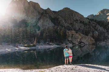young couple in  Yosemite, USA: Mountain landscape with mirror lake surrounded by high peaks