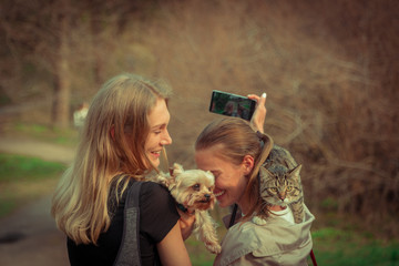 Selfy. A girl with a cat on her shoulder takes a girl and a dog