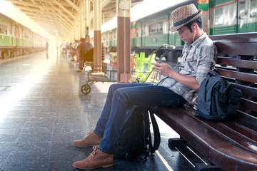 Asian man wearing a hat weave sitting playing games on mobile. While waiting for the train. At station in the outbound platform.