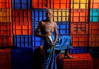 A worker eats puffed rice at a wholesale fish market in Kolkata