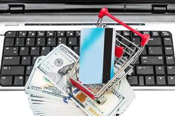 Shopping cart with credit card and money on keyboard of laptop. Top view. Close up. Online shopping. E-commerce.