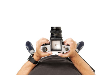 A man is holding a medium-format camera. View from above. Isolated on white background