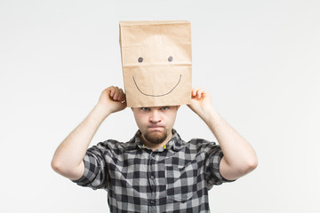 Angry white men wearing happy paper bag mask on white background