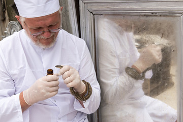 Elderly man is veterinarian in white coat and rubber medical gloves, holds snake in his hands and examines it against the background of a mirror. Steppe rats (Elaphe dione). Concept Respect for nature