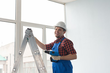 Happy male builder standing on ladder with drill infront of window.
