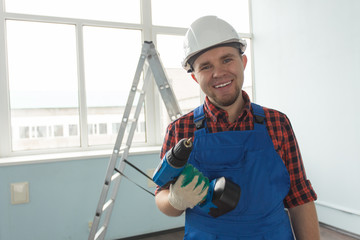 Closeup portrait of happy white male builder with drill wearing white helmet.