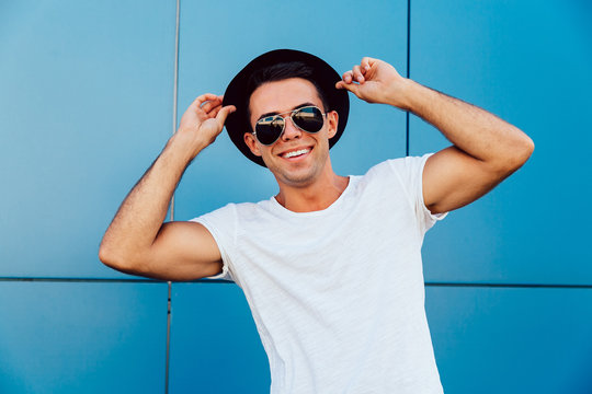 Funny young man in sunglasses, posing outdoors and looking at camera, holding his hat with both of hands. Dressed in white t-shirt.