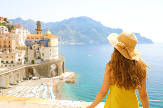 Summer holiday in Italy. Back view of young woman with straw hat and yellow dress with Atrani village on the background, Amalfi Coast, Italy