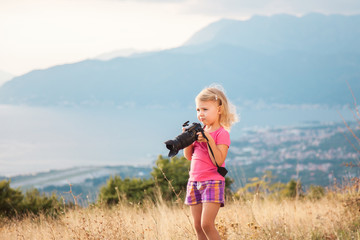 Little kid is playing with camera and taking photo of sea and mountains as master. Blonde girl is traveling photographer.