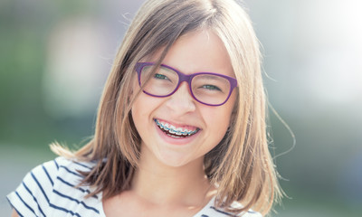 Portrait of happy smiling girl with dental braces and glasses