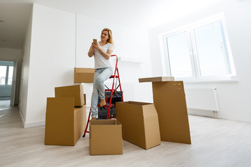 People moving new place and repair concept happy young woman with many boxes