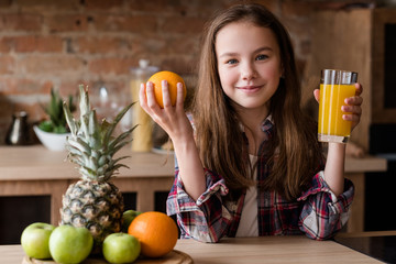child healthy food and balanced nutrition. fresh orange juice and fruit breakfast. little girl in the kitchen ready to have a wholesome morning meal
