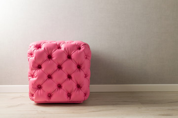 Furniture in the room. Pink pouf with decoration buttons in the home interior