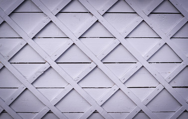 gray wooden fence with square lattice. vignette, background, texture.