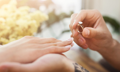 Man putting on girl finger engagement ring