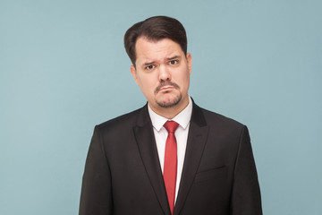Sad, looser businessman, crying, looking at camera and hope. Need a new job and money. isolated on light blue background. handsome businessman with black suit, and mustache looking at camera.