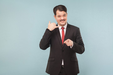 Printed kitchen splashbacks Artist KB Call center. Businessman showing phone sign and smiling. indoor studio shot. isolated on light blue background. handsome businessman with black suit, red tie and mustache looking at camera.